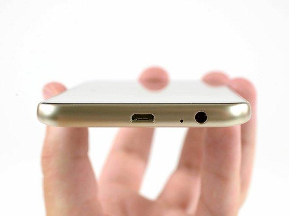 Enquanto procuramos por parafusos no lado de fora do smartphone, registramos a boa e velha porta de carregamento micro USB. E, logo a seu lado, um  conector de entrada para fone de ouvido.