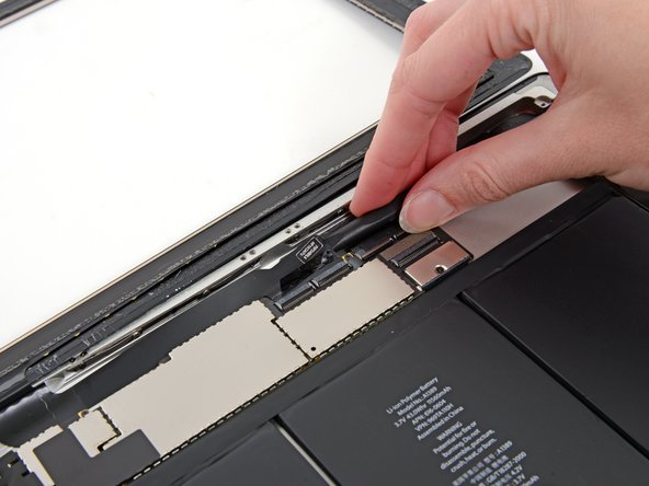 Use the flat end of a spudger to loosen the adhesive underneath the digitizer ribbon cable.
