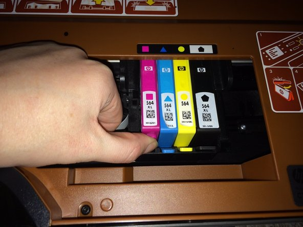 Press down gently on the front tab of the ink cartridge that needs replacing and then lift up.