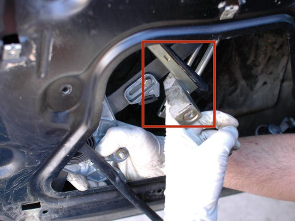 The outside window rail can now be rotated inside the door, towards the car, to make room for the window regulator and motor to pass it and come out of the opening in the door shell. Be sure to make note of how the rail and regulator are positioned so you can re-install them in the correct order/orientation.