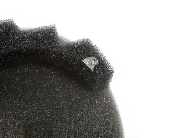 The protective cloth in the inside of the ear cups is glued to small foam spacers. These foam spacers are glued to  the headphone frame with small pieces of adhesive tape. During the following step make sure to remove the protective cloth including the foam spacers and not to rip the cloth off them.