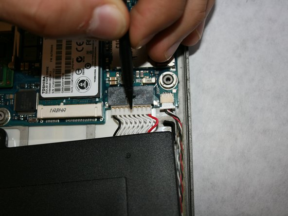 Using the nylon spudger, disconnect the white plugin.