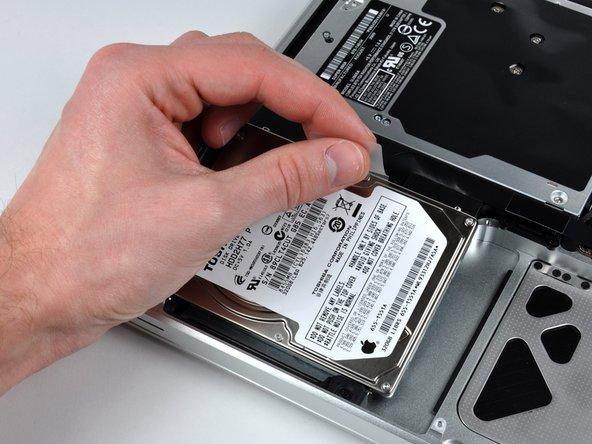 Til de harde schijf op door deze vast te pakken bij de treklip en uit het chassis te trekken. Let hierbij wel op dat je de kabel die de harde schijf nog aan de laptop verbindt niet beschadigt.
