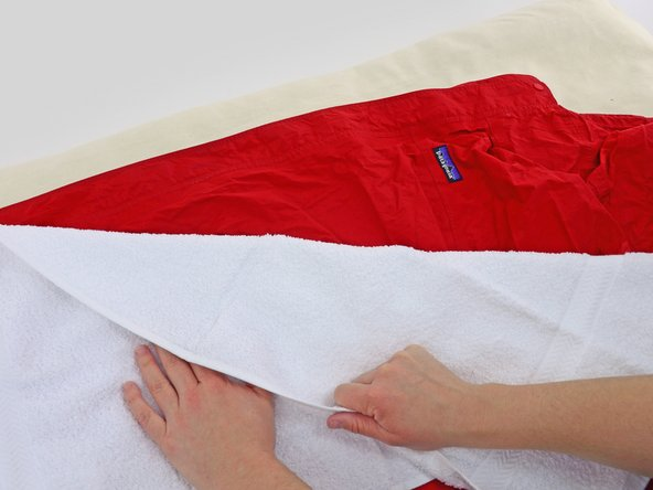 Lay a towel over the area of your jacket that you'll be ironing.