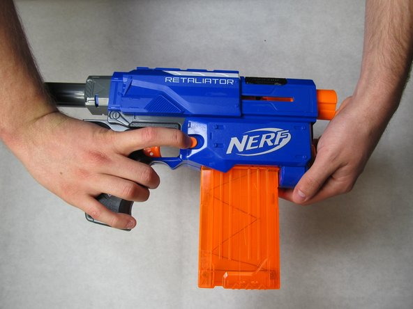 Remove the magazine from the blaster by forcing the sliding mechanism backwards, pushing the orange tabs downward, and pulling the magazine away.