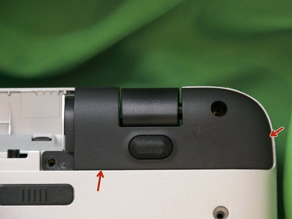 Use a guitar pick to release the plastic clips at the points shown on the black covers near the hinges.