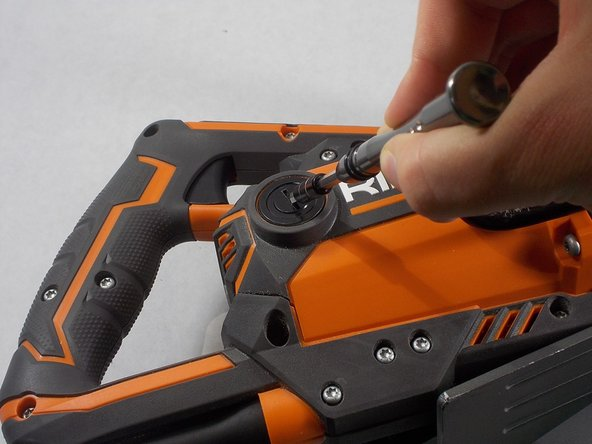Using a flathead screwdriver, remove the motor brush cap from the main housing assembly.