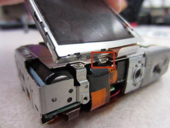 Lift the LCD screen up and away from the tab that holds it in place on the face of the camera.