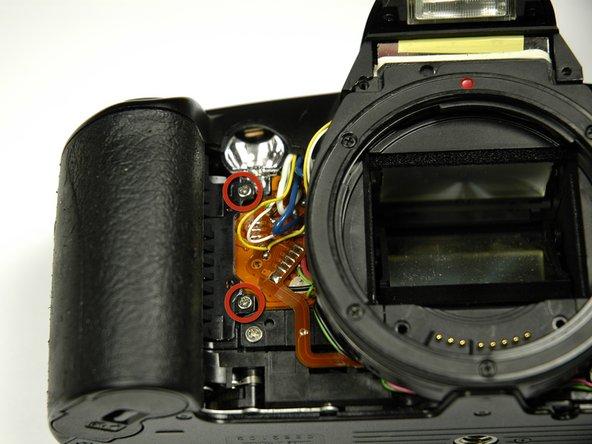 Using a 00 Phillips screw driver, unscrew the two 4.9 mm Phillips screws. on the inside of the camera.