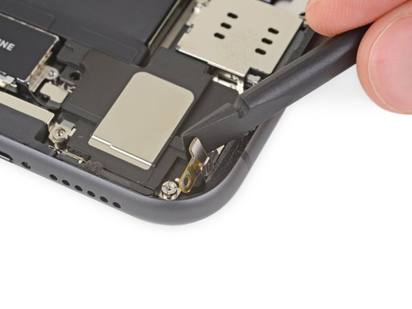 Lift and push aside the small board covering the remaining speaker screw in the bottom right corner of the iPhone.