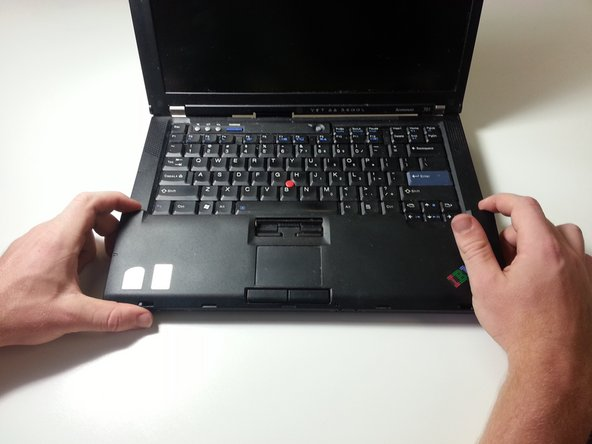 Turn the computer over so the keyboard is facing upwards, and open the Thinkpad.