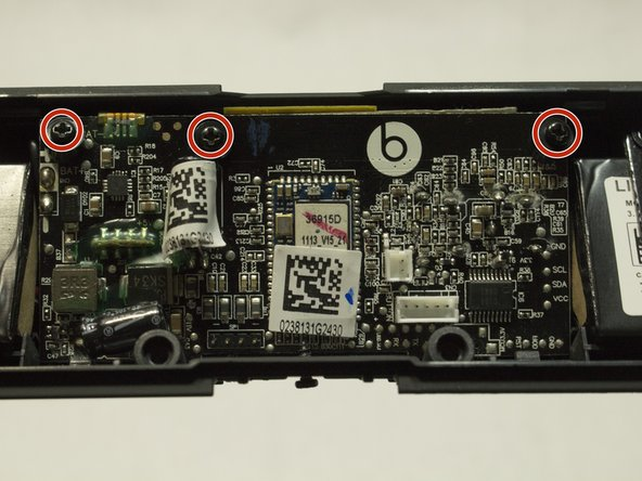 Remove the three 9 mm screws from motherboard and rubber stopper using a Phillips #0 screwdriver.
