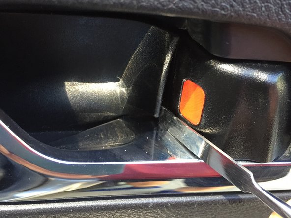 """Remove the black plastic cover """"plate"""" behind the door handle.  I pulled open the door handle and used a metal spudger in the lower right corner to pop out this cover plate."""