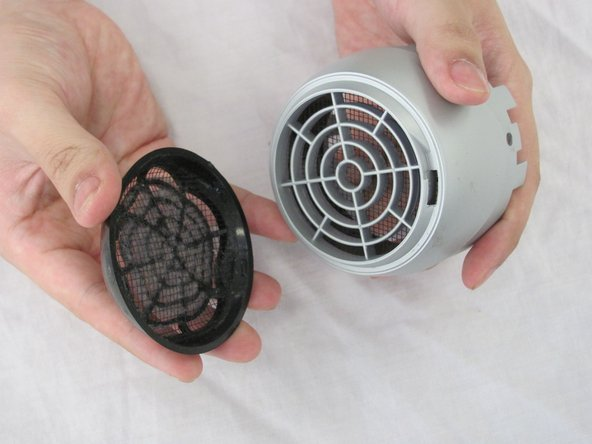 Remove the black vent from the grey cylindrical piece.