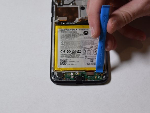 Using the iFixit opening tool, carefully pry up the charging port assembly.