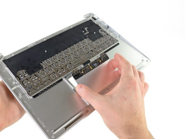 Carefully lift the edge of the trackpad closest to the keyboard from its recess in the upper case by lifting it away from the brackets attached to the upper case.