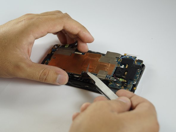 Lift the motherboard completely out of the phone. (may stay attached at the bottom by tape)