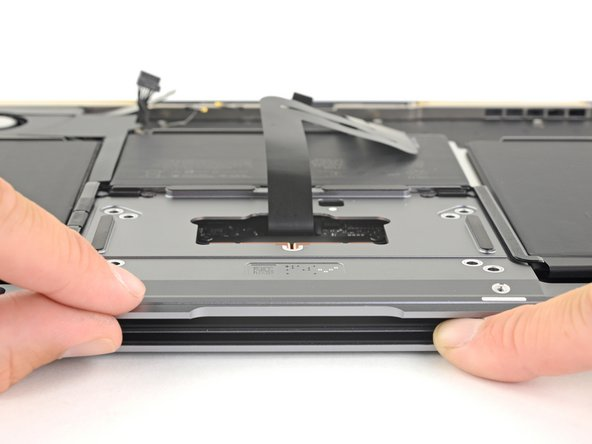 With the laptop still lying screen-side down, carefully open the laptop. The trackpad will stay sitting on the display.