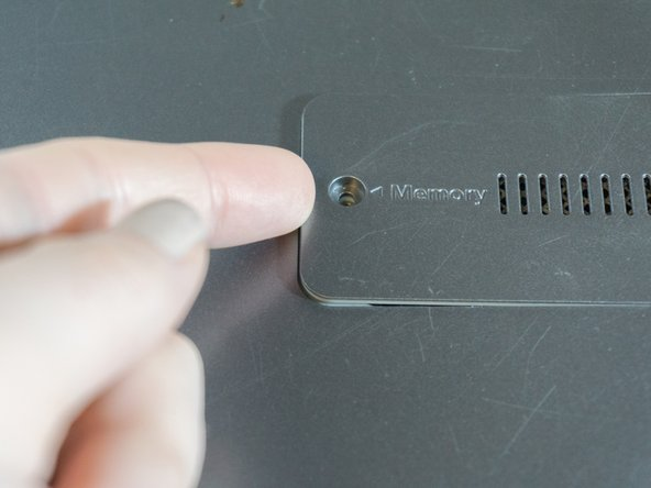 Wedge your finger underneath the edge of the memory cover. Grasp and pull the cover to the left to remove it.