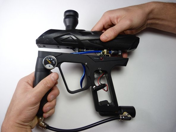 Separate the gun's body from the frame by gently pulling them in opposite directions.