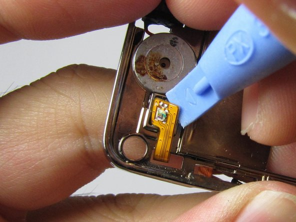 Pry the rest of the orange connector pad --on the opposite side of the device-- away from the frame, and carefully remove the entire earpiece.