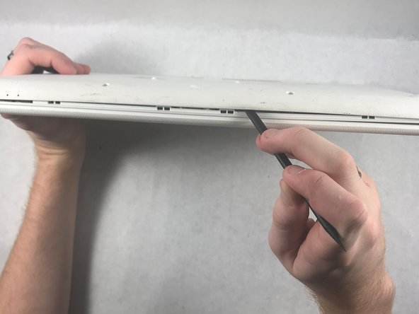Using the flat side of the spudger,  pry open the bottom case of the laptop.
