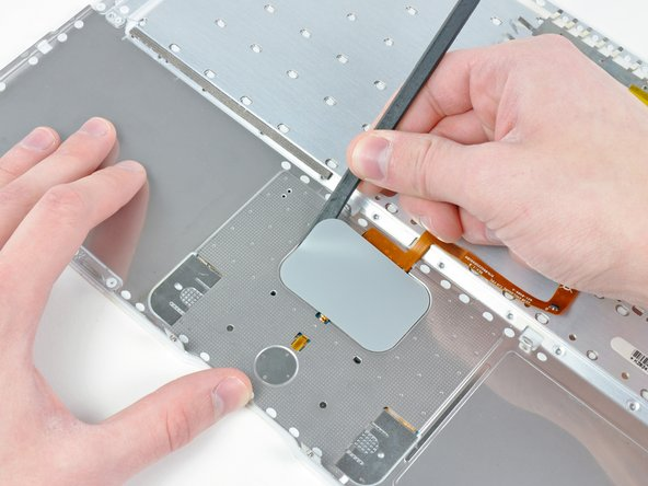 Use the flat end of a spudger to carefully peel up the adhesive around the perimeter of the plastic panel stuck to the underside of the trackpad.