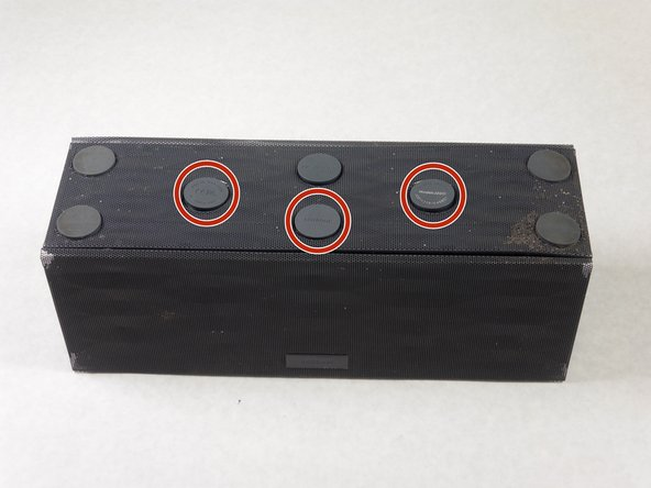 Turn the Jambox upside down. Peel the indicated rubber tabs off, using a plastic opening tool if necessary.