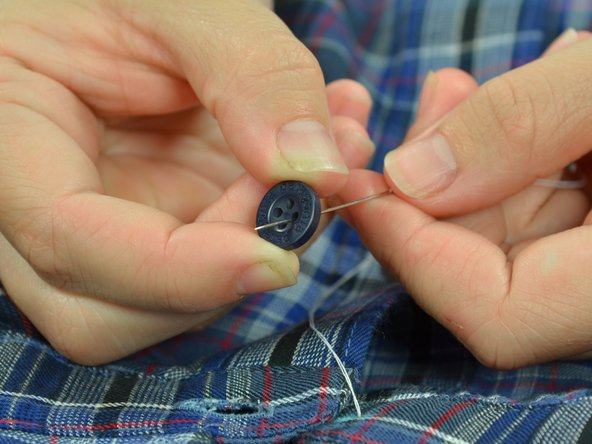 Thread the needle through one hole of the button. You can pick any hole to start with.