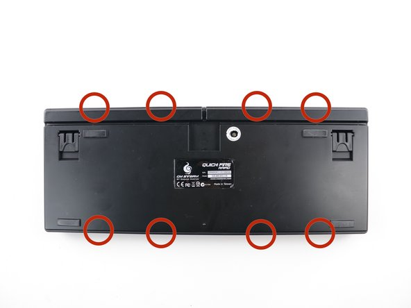 Wedge a plastic opening tool between the rear plate and rim of the keyboard and slide it through the circled areas to separate the plastic hooks that mount the rim to the rear plate.