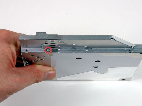 Rotate the drive and remove the single Phillips screw securing the mounting bracket to the right side of the optical drive.