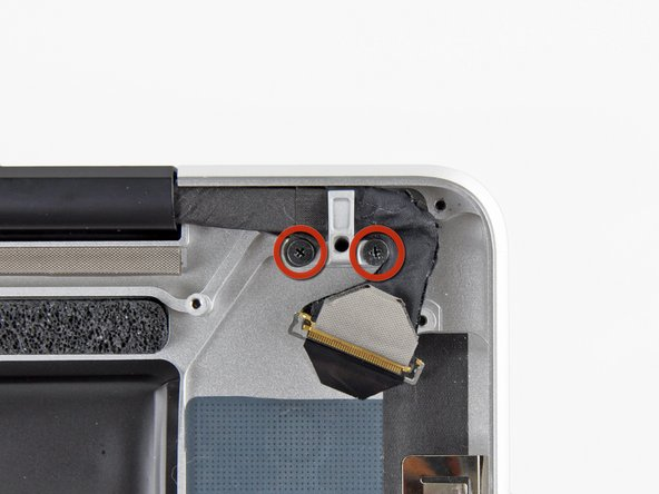 Remove the two 7.1 mm Phillips screws securing the display data cable retainer to the upper case.