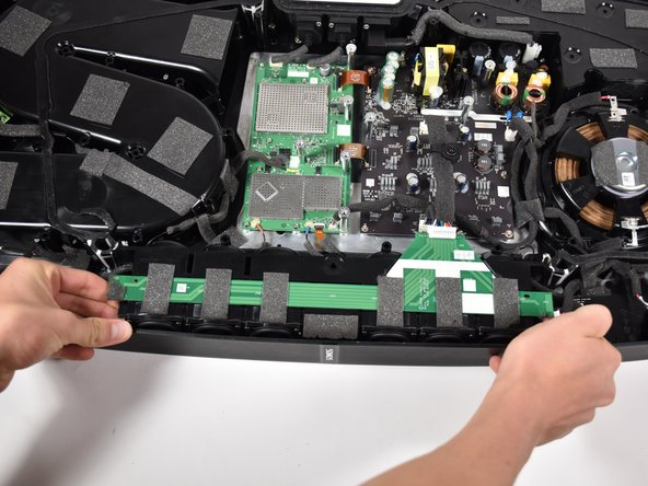 Remove the main speaker array by gripping it on both sides and pulling it out.