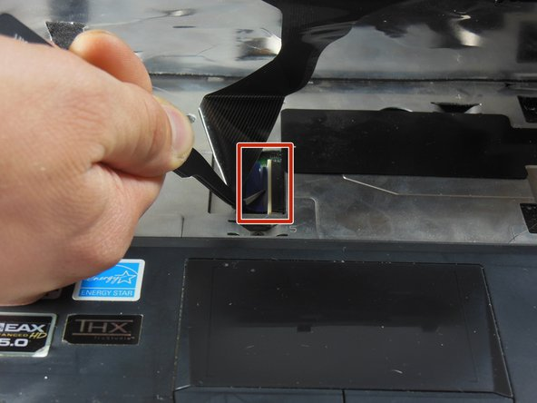 Just above the trackpad, there is a second, wider ribbon cable connected to the motherboard. Unplug this cable.