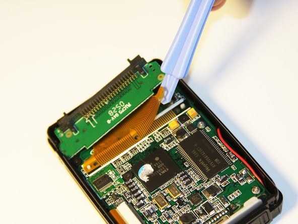 Using the plastic opening tool, completely lift the ribbon off of the motherboard.