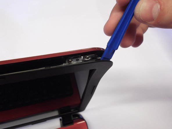 Slide plastic opening tool in crack at the top corner of the outer frame of the screen (in the gap between the red and black sections of plastic) and pry apart as shown.
