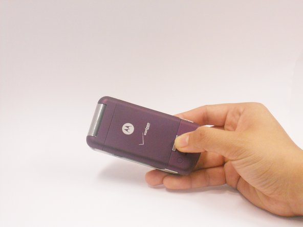 Using your finger, press down on the clip holding the back cover on