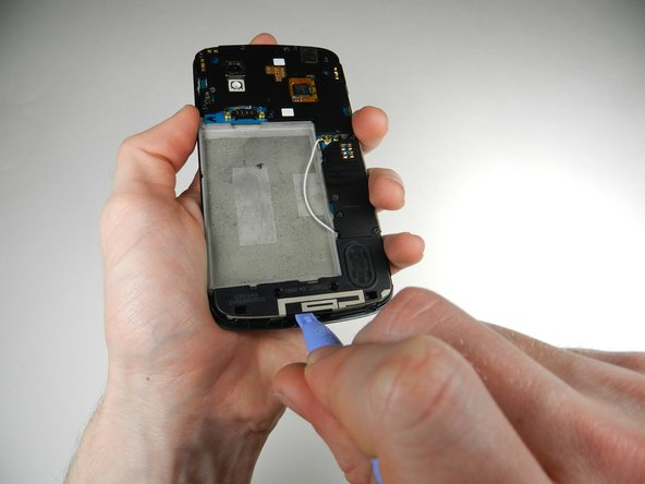 Gently pry the speaker up and away from the back of the phone using a plastic opening tool, and lift it out of the phone.