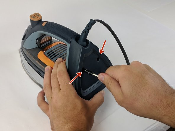 Use the Philips head #0 screwdriver to remove the two 11.49mm screws at the back of the iron.