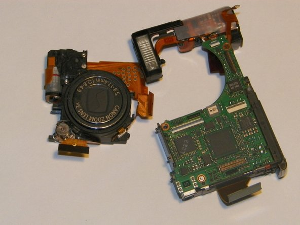 Firmly gripping the front and rear of lens, gently remove the assembly from between the motherboard and the flash assembly.