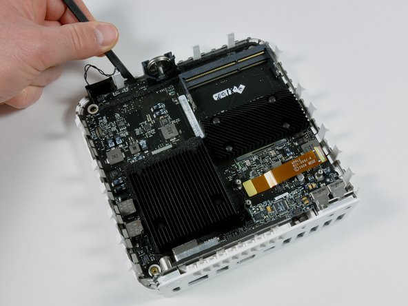 Use a spudger to gently pry up the logic board.