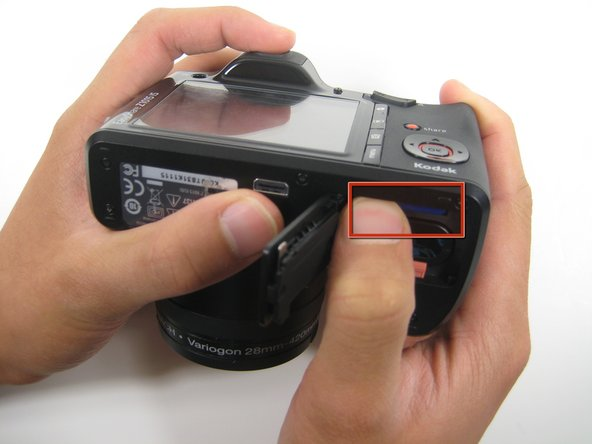 After locating the SD card, gently push down on the card and release. This will cause the SD card to pop out of its position in the camera as shown in the second picture of this step.