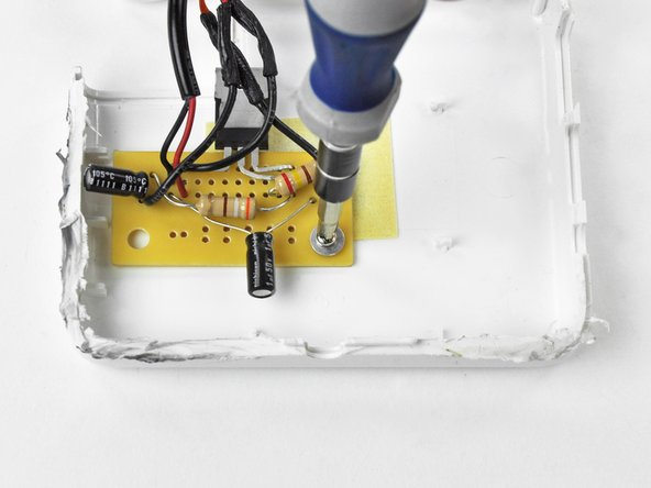 Secure the PCB to the upper case half  using the original 5.38 mm #1 Phillips screw and the included washer.