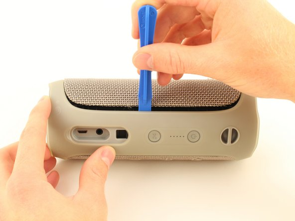 Insert the plastic opening tool in the crack in between the cover and the rubber spine with the power button.