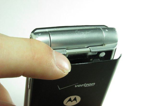 Using your finger, press down on the clip holding the back cover on.