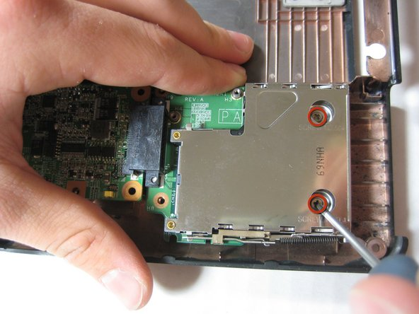 Remove the two 3.8 mm Phillips screws securing the right edge of the expansion port board to the motherboard.