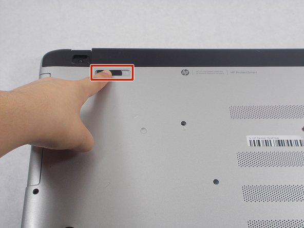 Slide the battery lock (the switch at the upper left corner of the laptop's underside) to the right until it clicks into place.