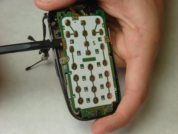 Using the spudger, start to gently pry the motherboard from the back of the phone and work your way around the perimeter of the motherboard.