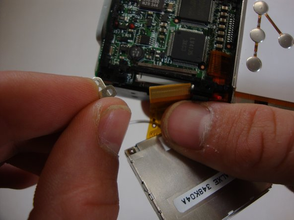 Remove the bottom left LCD mounting frame screw. The screen should come loose after the screw is removed.