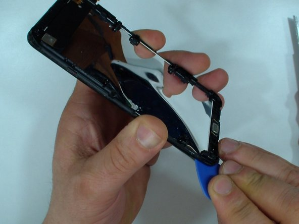 Carefully put the plastic tool between the glass and the LCD.